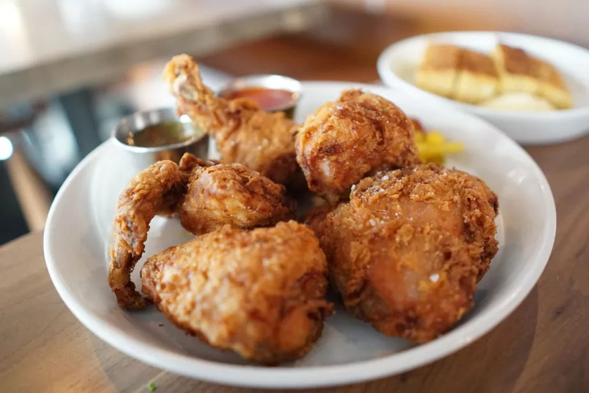 A picture of five pieces of golden fried chicken at Bullard, served in a bowl with side sauces