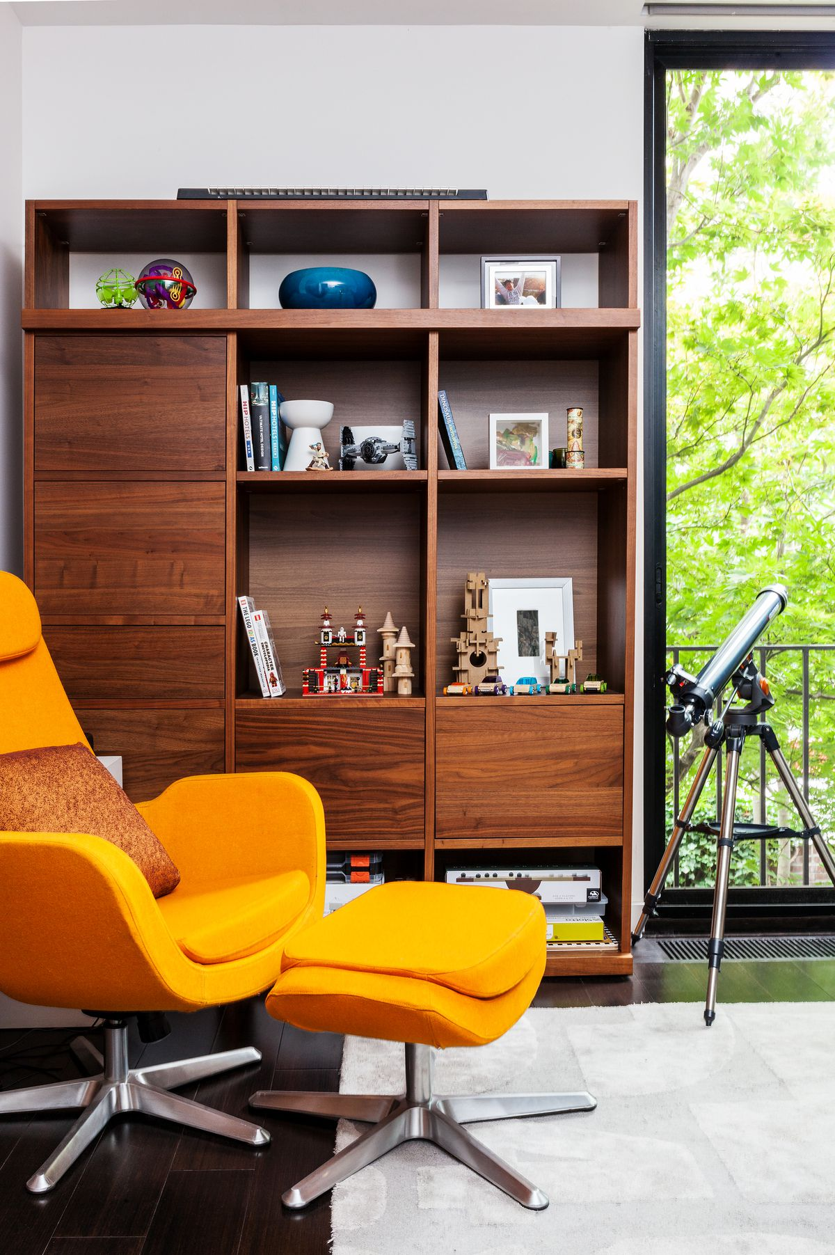 A bright orange armchair sits in front of a walnut shelf.