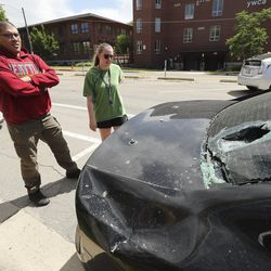 Joshua Fereday and his girlfriend, Liz Mutz, look over damage to his car in Salt Lake City on Sunday, May 31, 2020, after demonstrators damaged it while he was driving Saturday. Daylong protests moved across the city Saturday after a peaceful demonstration to decry the death of George Floyd in police custody in Minneapolis turned violent. Protesters vandalized buildings throughout the downtown area before a curfew was enforced in the evening.