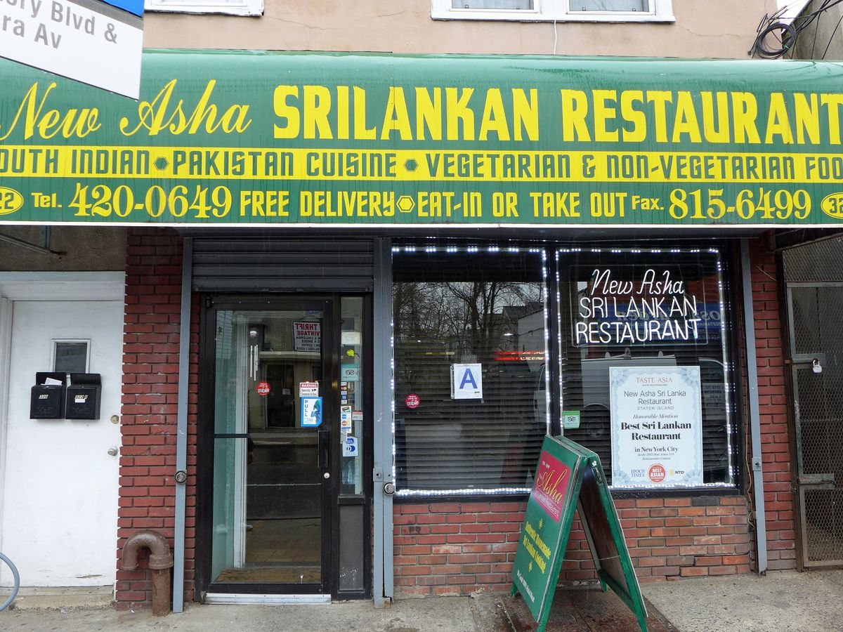 """The front of a storefront with a green awning that with the words """"New Asha Srilankan Restaurant"""" in all capital yellow letters"""