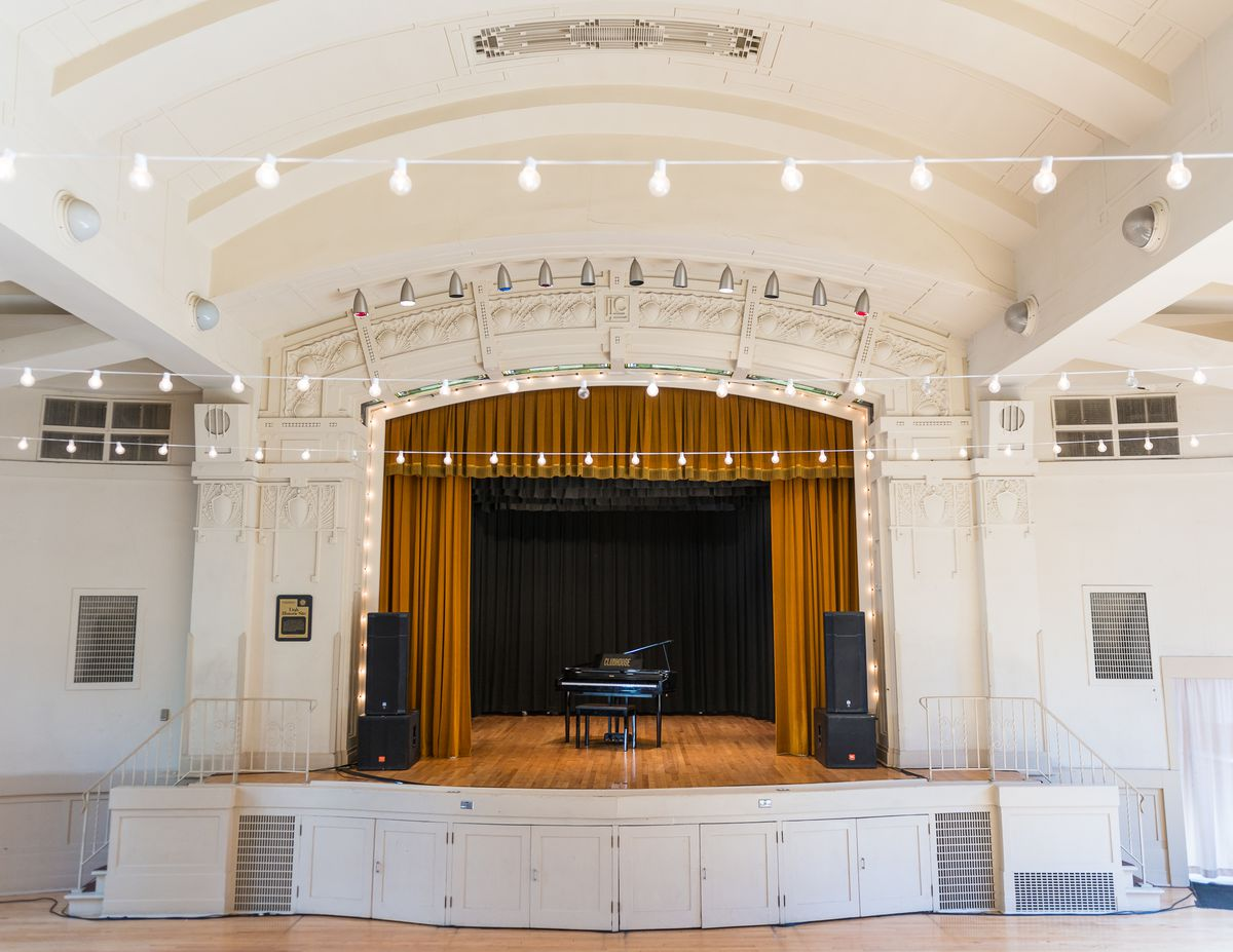 A white room has a stage in the center with wooden floors and brown curtains. A black grand piano sits in the center of the stage.