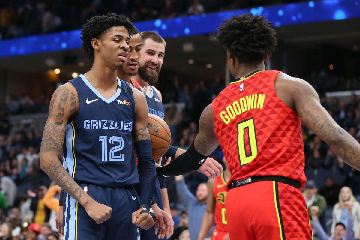 Memphis Grizzlies guard Ja Morant (12) reacts after scoring as center Jonas Valnciunas (17) and Atlanta Hawks guard Brandon Goodwin (0) look on at FedExForum. Memphis won 118-101.