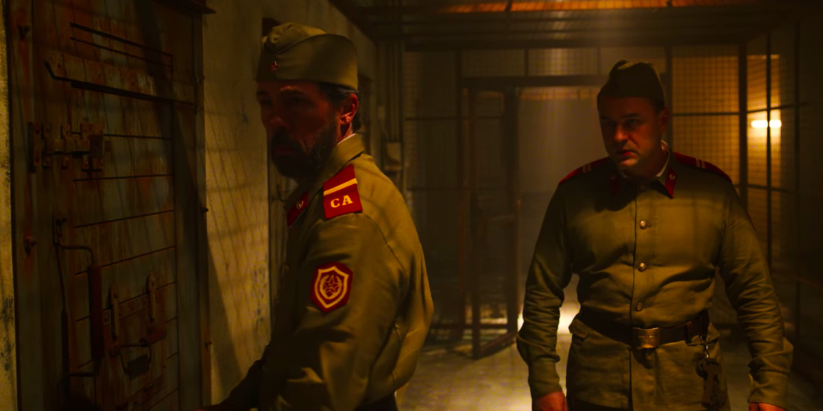Two Soviet soldiers stand in an a dark hallway with bars on one side. One soldier is unlocking a door while the other watches.