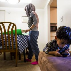 Nour Bilal, 15, does homework while her brother, Zain , 3, plays on a phone at their home in Millcreek on Tuesday, Sept. 8, 2015.