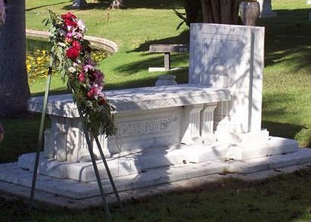 An above ground gravesite. The stone coffin has a sign that reads Tyrone Power. There is a decorative flower display in front of the gravesite.