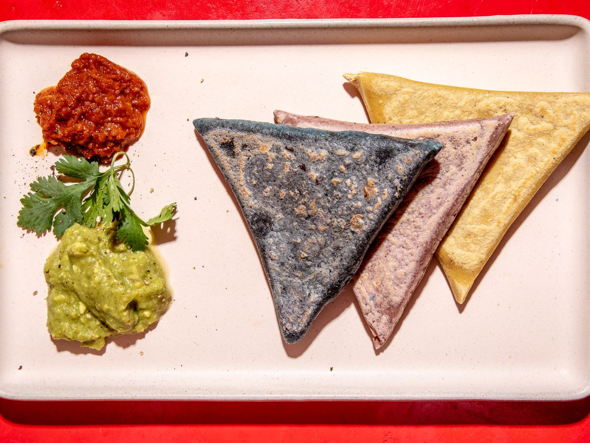 A trio of tetelas, blue red and yellow, sit on a white plate next to piles of red and green salsa