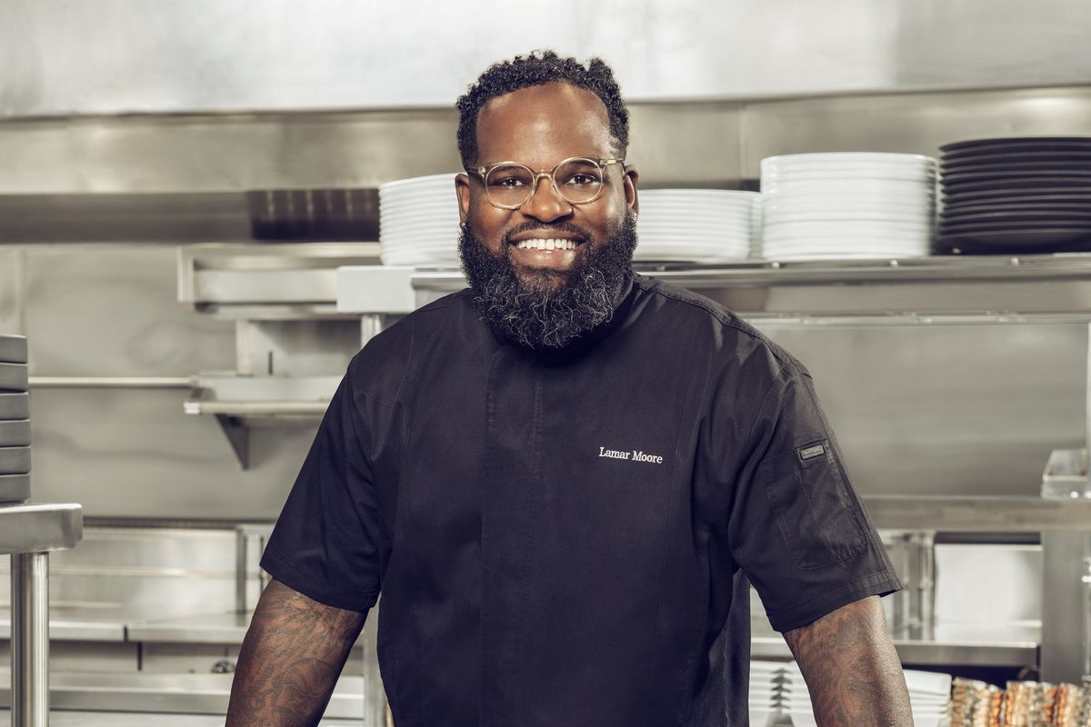 A chef stands in front of meat in a kitchen