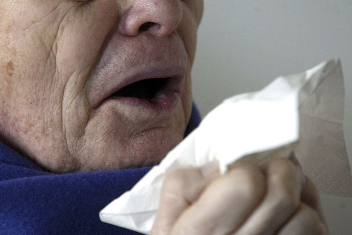 A man sneezes holding a tissue in Berlin, Germany.
