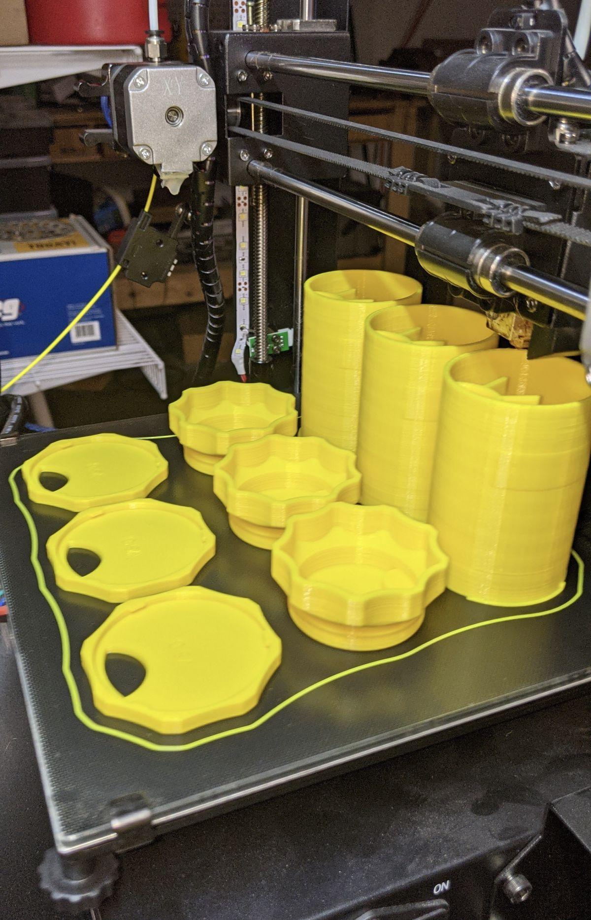 Three yellow bottles, three hats, and three bases sitting on a 3D printer.