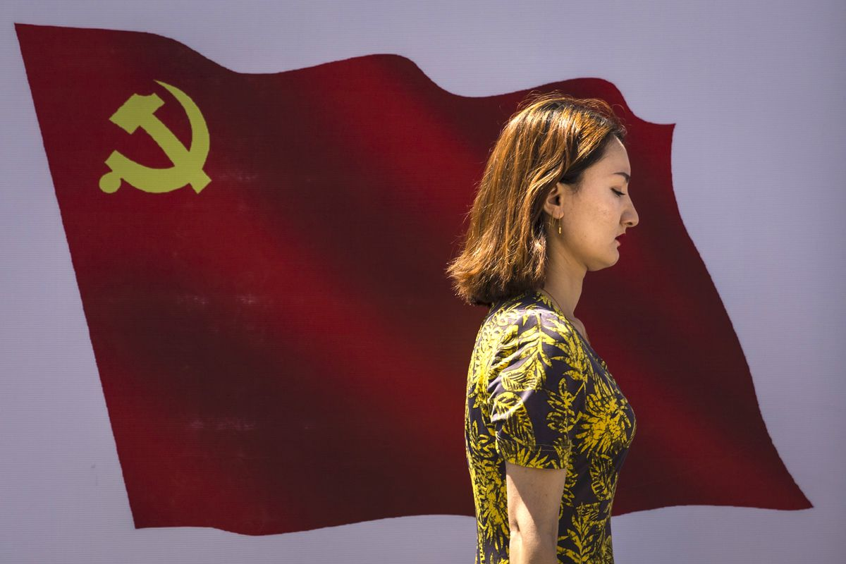 A Uighur woman passes the Communist Party of China flag on the wall in 2017 in Urumqi, China.
