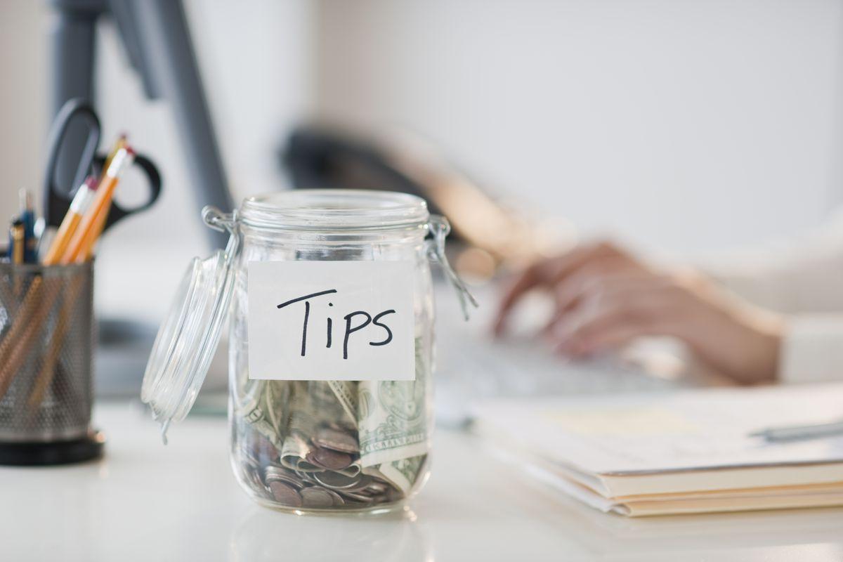 A tip jar on an office desk.
