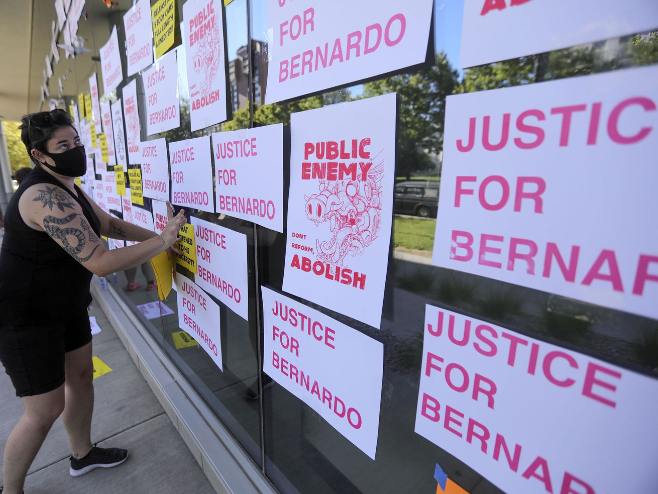 Kaitlyn Mahoney hangs a sign on the Salt Lake County District Attorney's Office during a rally in Salt Lake City on Monday, June 22, 2020, denouncing the death of Bernardo Palacios-Carbajal, who was shot and killed by Salt Lake police in May.