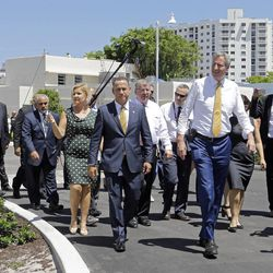 Miami Beach Mayor Philip Levine, foreground left, and New York City Mayor Bill de Blasio, foreground right, tour the area where the city has raised streets and installed pumps to combat rising tides, Friday, June 23, 2017, in Miami Beach, Fla. The U.S. Conference of Mayors opens its annual meeting Friday in Miami Beach. Mayors of cities with populations of 30,000 or more will discuss plans to reduce the nation's carbon footprint and protect immigrant families.
