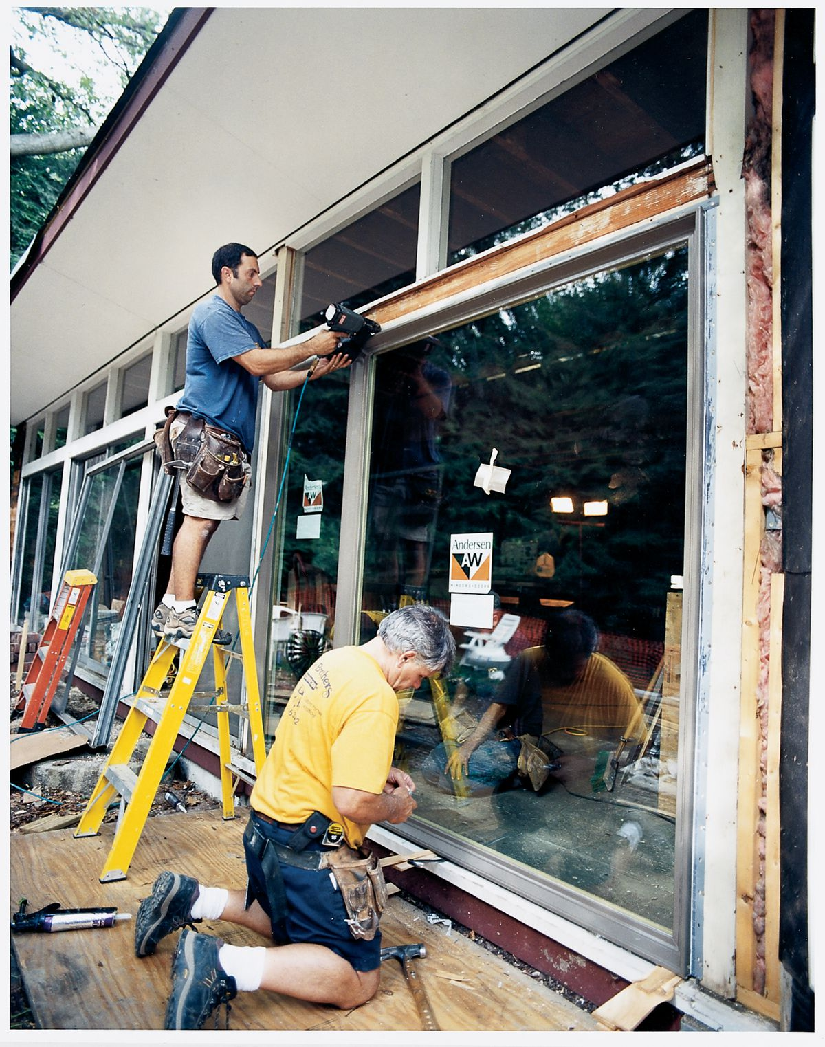 <p>Tom shims a window to make it level and plumb as he and one of his crew nail the strong fiberglass unit into place.</p>