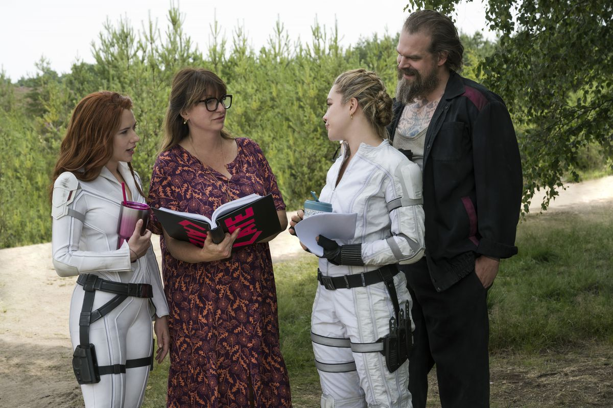 Scarlett Johansson, Cate Shortland, Florence Pugh, and David Harbour stand on the Black Widow set with an open script