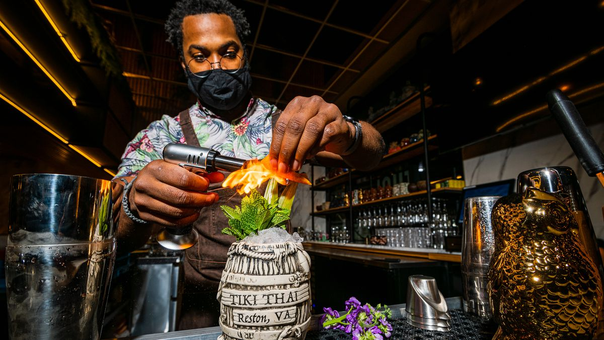 Tiki Thai beverage director and general manager Jeremy Ross lights a garnish on a Mai Tai #1 with aged rhum agricole and blended Jamaican rum