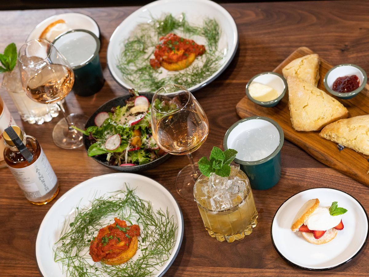 An angled photo shows a wooden table with a Mother's Day spread including bowls of fish and tomato, platters of scones, a bowl of salad, and drinks including rosé and mint juleps