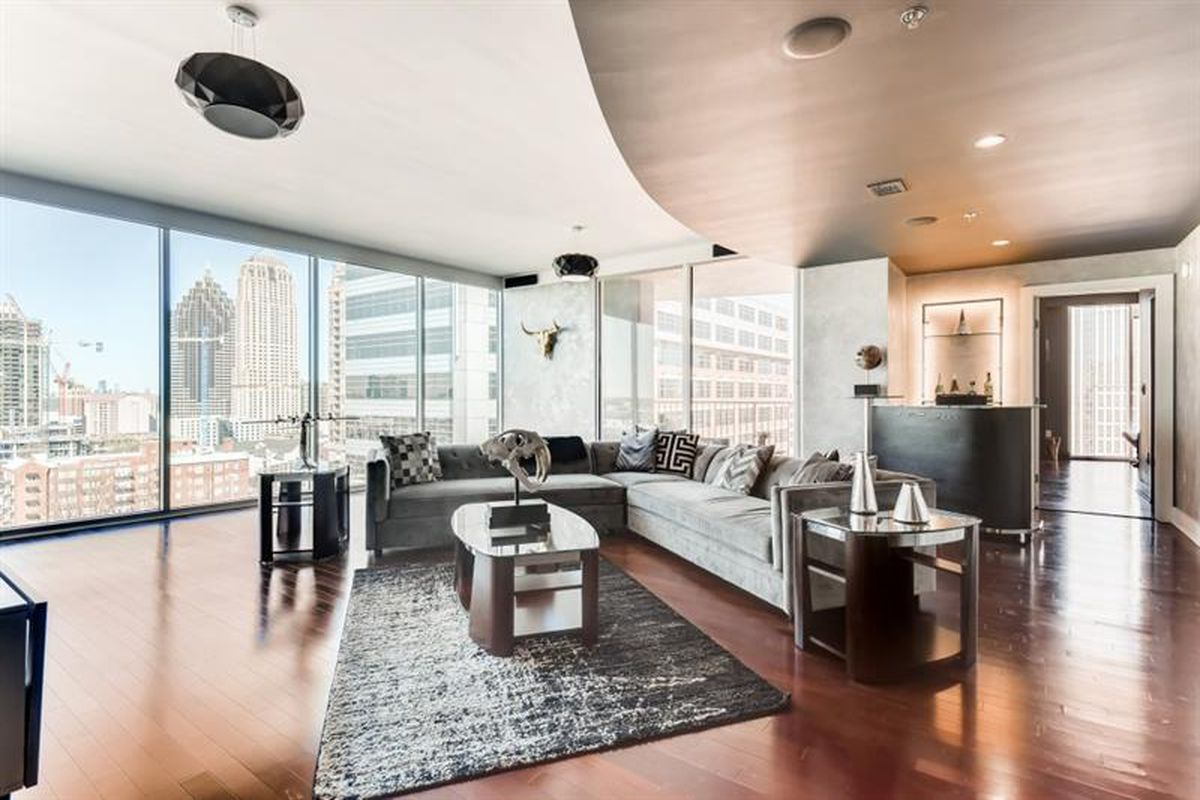 A large condo with black furniture, a kitchen island at right, and big views across a large city.
