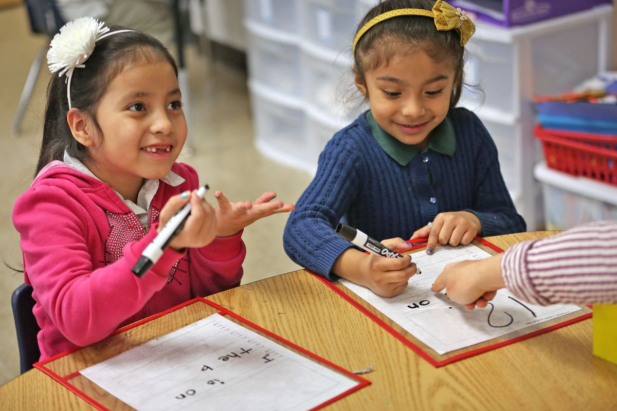 Kindergartners Ivania, left, and Jackie work on reading and writing with their teacher, Liz Amadio, at Enlace Academy.