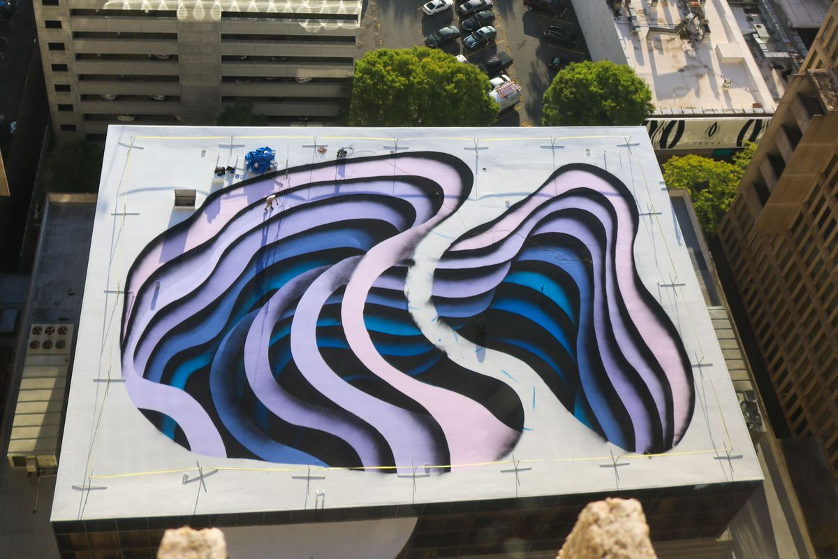A mural on the rooftop of a building presents an optical illusion, making it seem as if there are deep, dark crevices in the building.