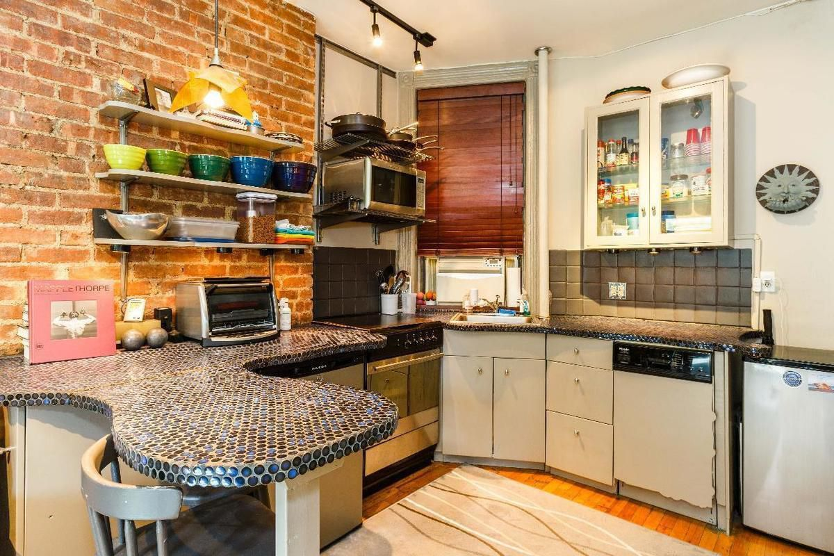 Located a block away from times square this sunny one bedroom with an open floorplan is asking 465000 its details include exposed brick a small kitchen