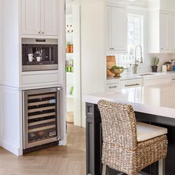 Modern appliances blend effortlessly with the white Shaker-style cabinetry in the new kitchen. At rear is the door to the pantry, which was once an outhouse attached to the historic home. <em>Kitchen appliance installation: Accurate Appliance Installations</em>