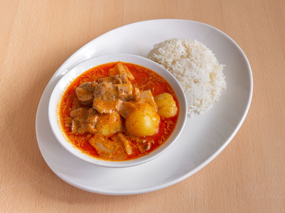 A beef massaman curry, brick-red with meat and potatoes, served in a bowl on top of a larger plate that also holds a pile of rice