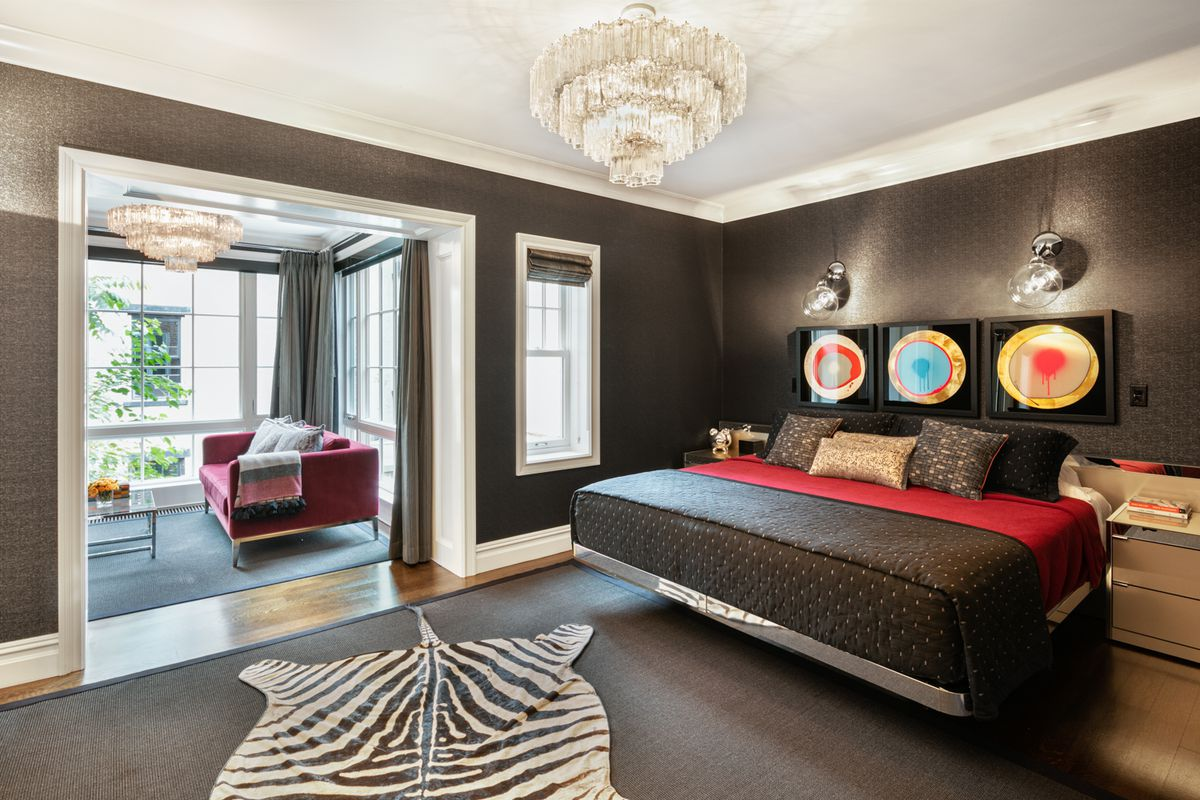A bedroom with a black wallpaper, a black rug, a large bed, and two nightstands.