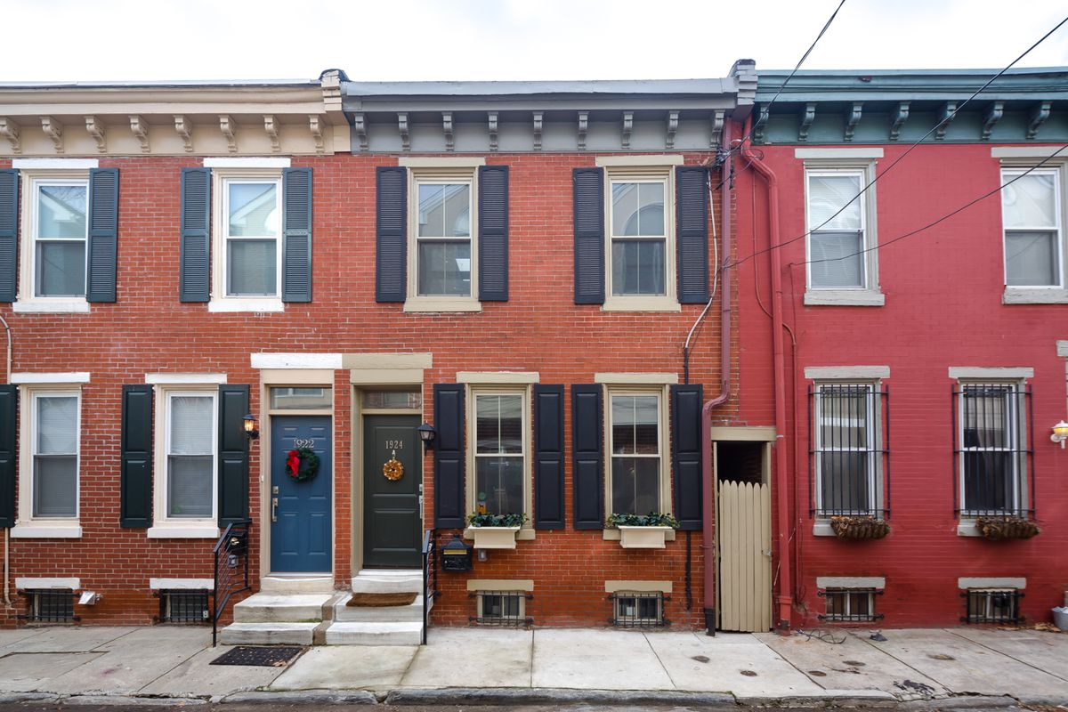 A cute two-story brick rowhome with a gray cornice, black window shutters, and flower boxes.