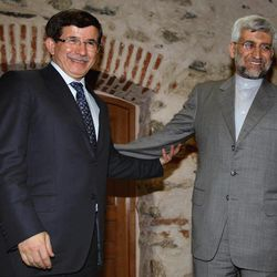 Turkey's Foreign Minister Ahmet Davutoglu, left, and Iran's Chief Nuclear Negotiator Saeed Jalili pose for cameras before their meeting in Istanbul, Turkey, Friday, April 13, 2012. After years of failure, Iran and the six world powers may finally make some progress on nuclear negotiations when they meet again Saturday if each side shows willingness to offer concessions the other seeks.