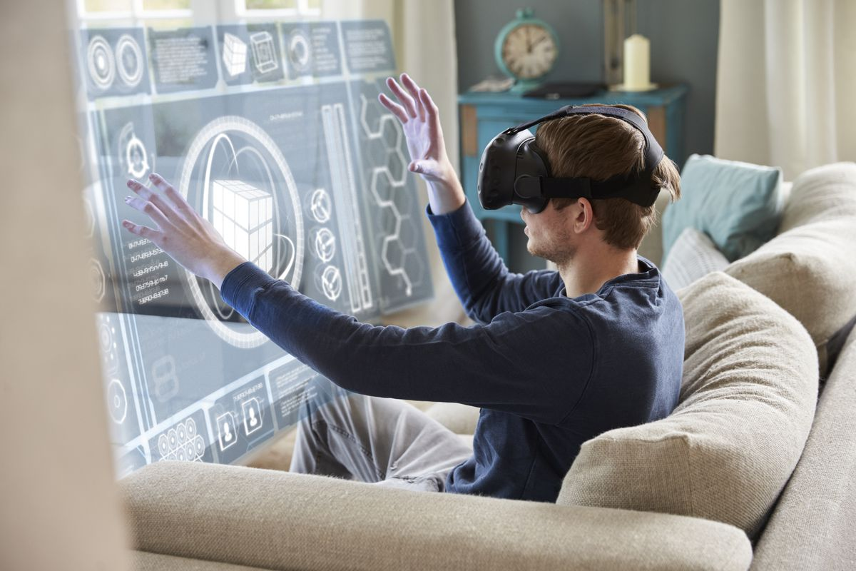 a man sitting on a beige couch wearing a VR headset and holding his hands out