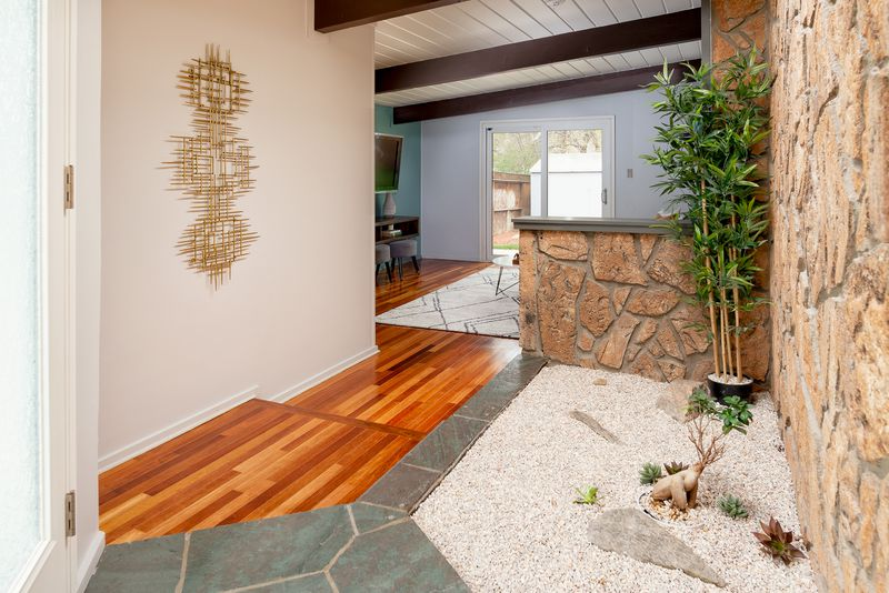 The interior entrance to the ranch home has wood floors and a small planter area with bamboo, white rock, and a wall of moss rock.
