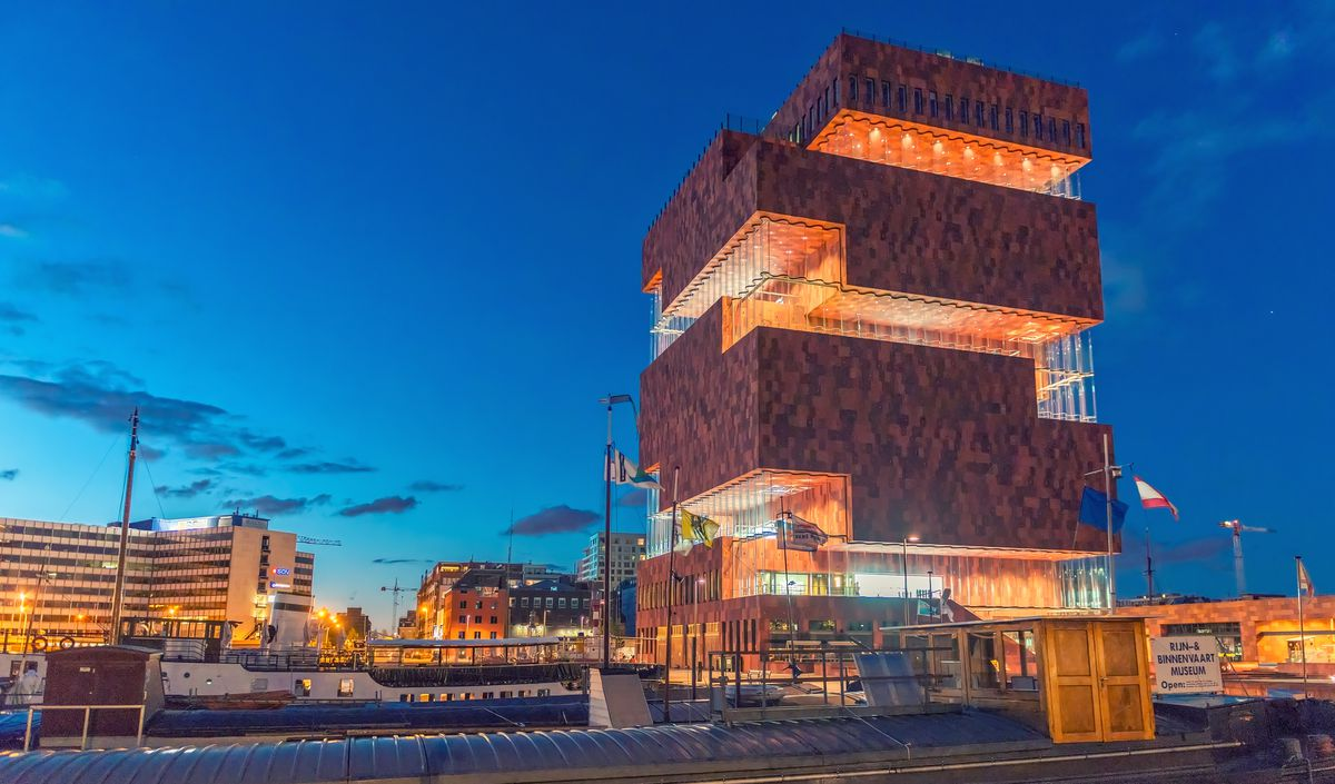 The exterior of the Museum aan de Stroom in Belgium. The geometric facade is brown and orange consisting of brick and glass. It is evening and the sky is dark blue.