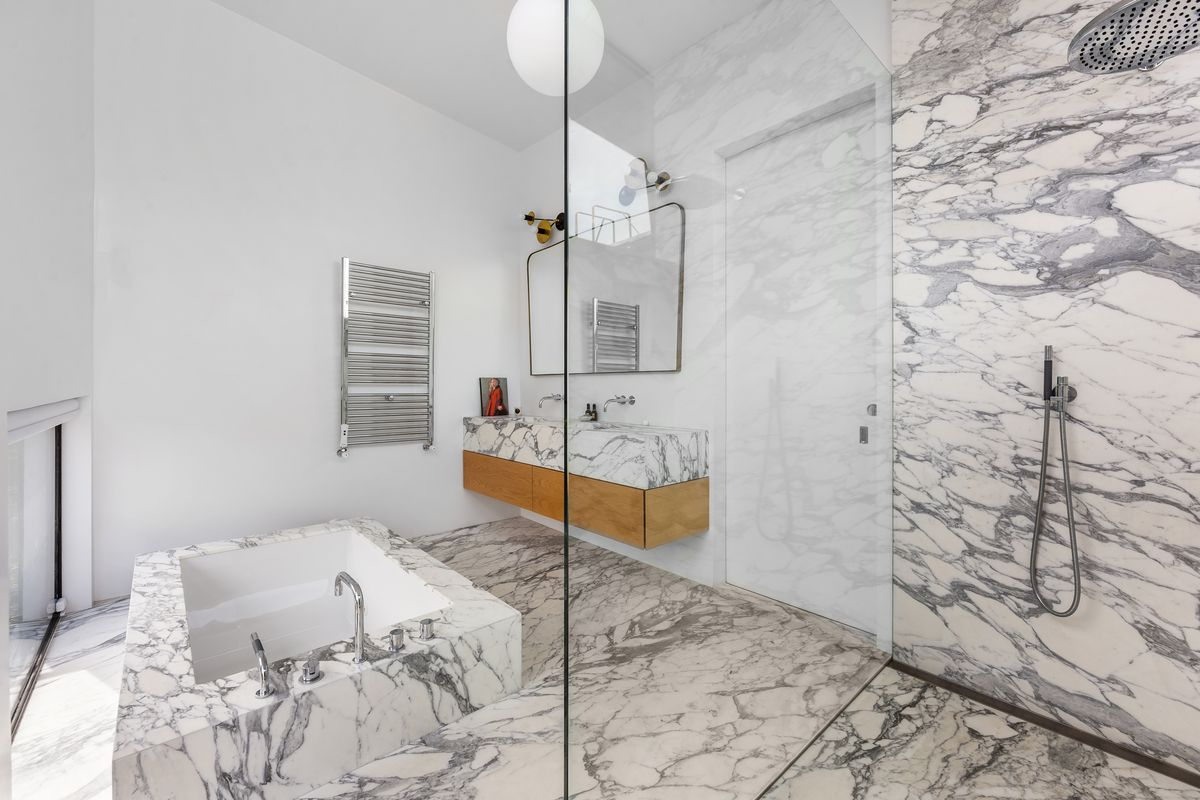 A bathroom with marble-covered walls, a deep tub, and a shower stall.