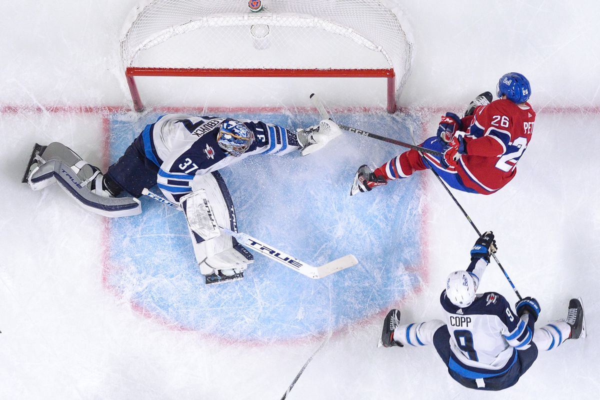 Connor Hellebuyck #37 of the Winnipeg Jets defends the goal against Jeff Petry #26 of the Montreal Canadiens in the NHL game at the Bell Centre on April 30, 2021 in Montreal, Quebec, Canada.