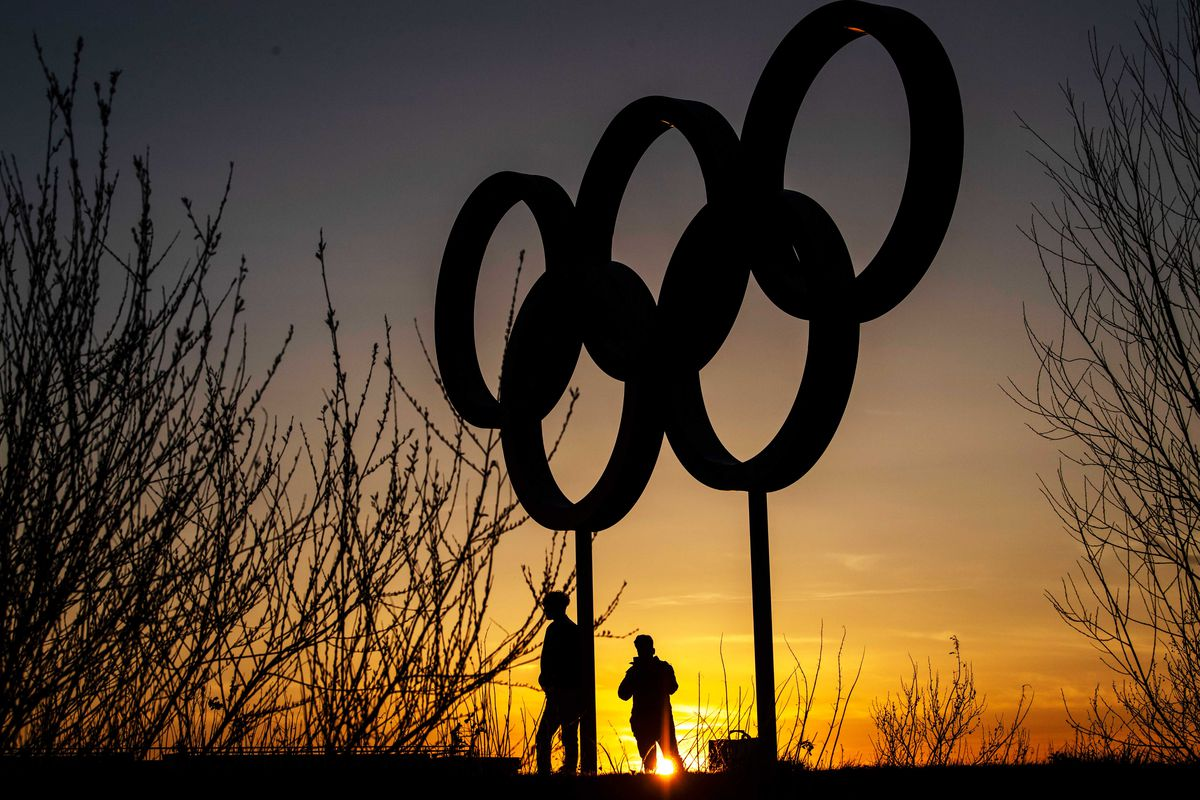 Two people in silhouette beneath the Olympic rings symbol standing in an open park.