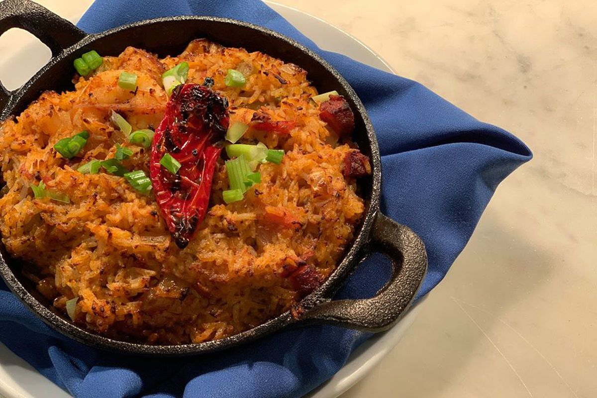 Yellow rice fills a cast iron pan, garnished with green onions and a grilled chile pepper. The pan sits on a blue cloth napkin.
