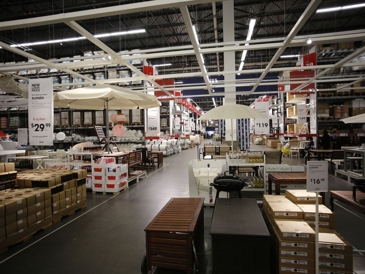 The interior of Ikea Brooklyn. There are many items of furniture on shelves and stacked on the floor.