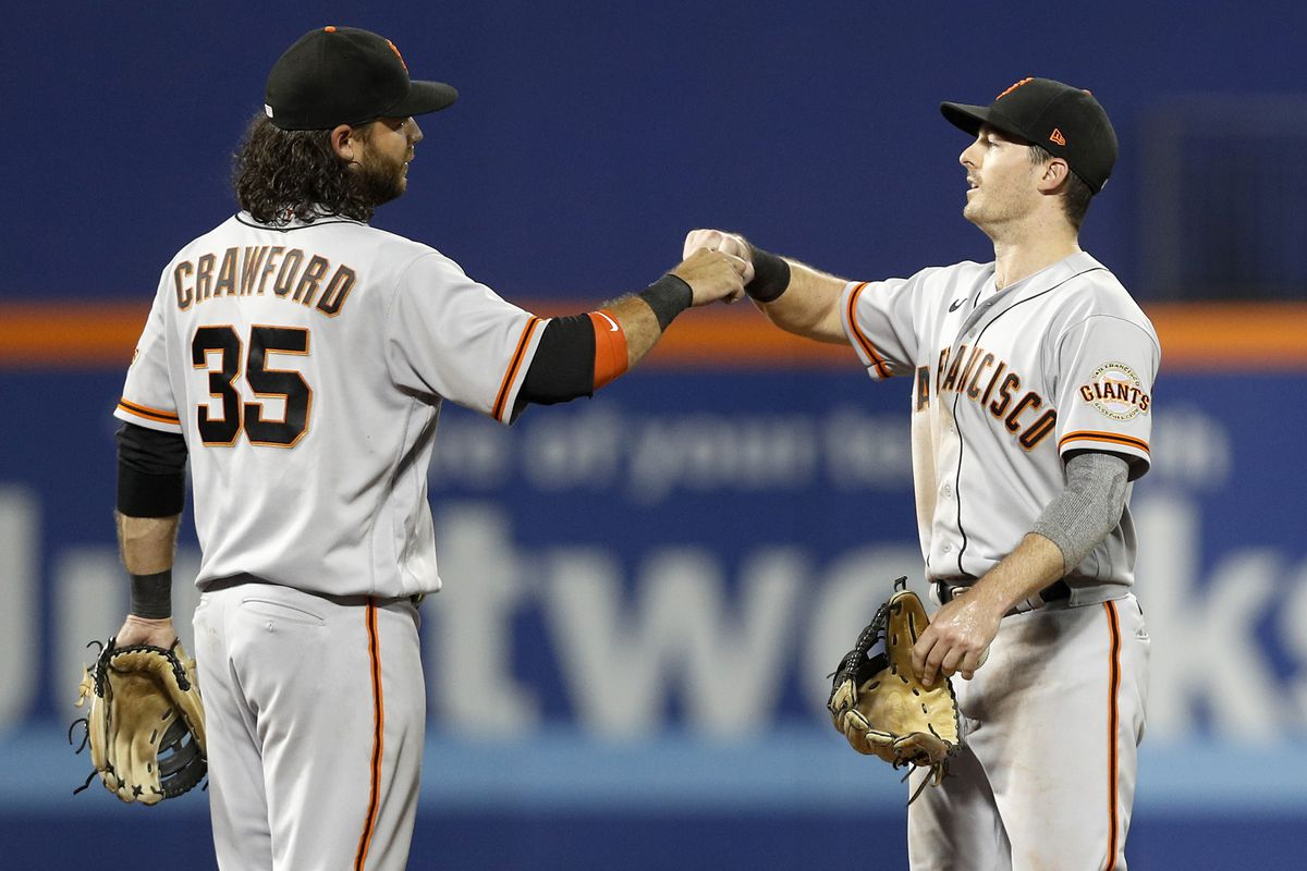 Brandon Crawford and Mike Yastrzemski of the San Francisco Giants celebrate after defeating the New York Mets at Citi Field on August 26, 2021 in New York City. The Giants defeated the Mets 3-2.
