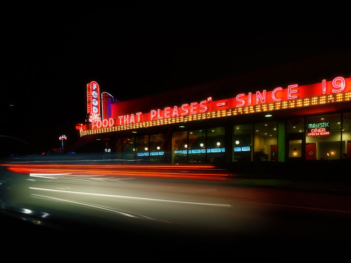 Nighttime shot of building with neon lights across the roofline.