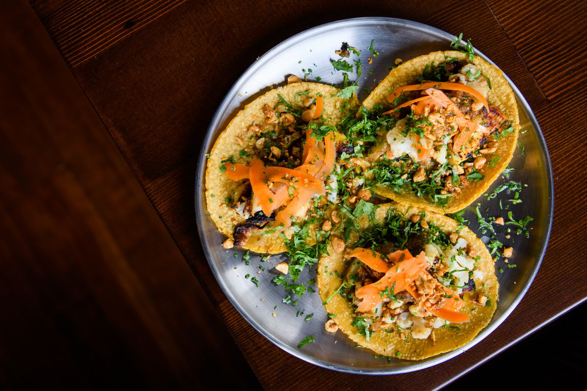 Three corn flour tortillas sit on a silver plate, topped with sweet potatoes, thinly shaved carrot, cilantro, and peanuts.