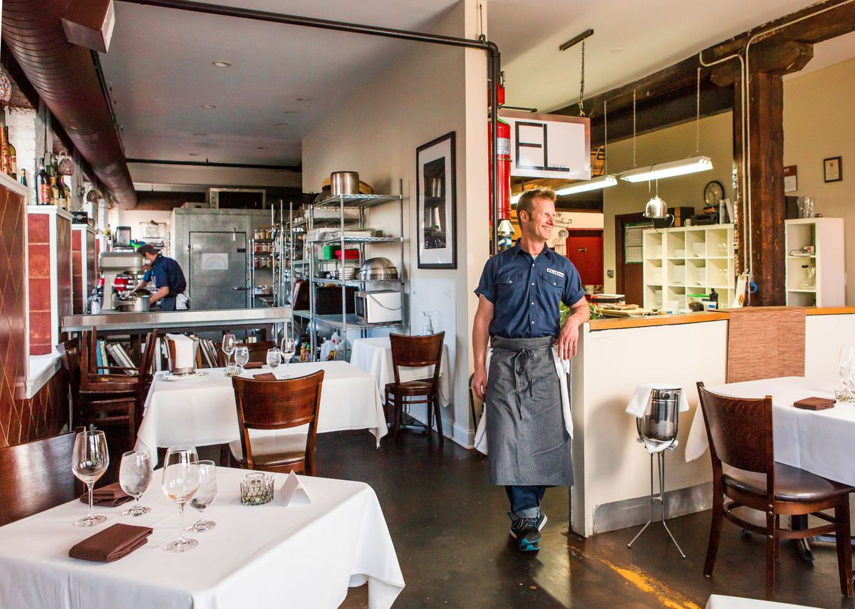 A white male chef stands inside a restaurant.