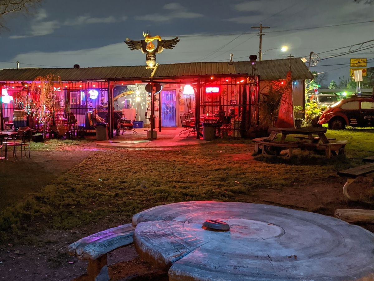 a large yard facing a neon-lit, low-sling dive bar