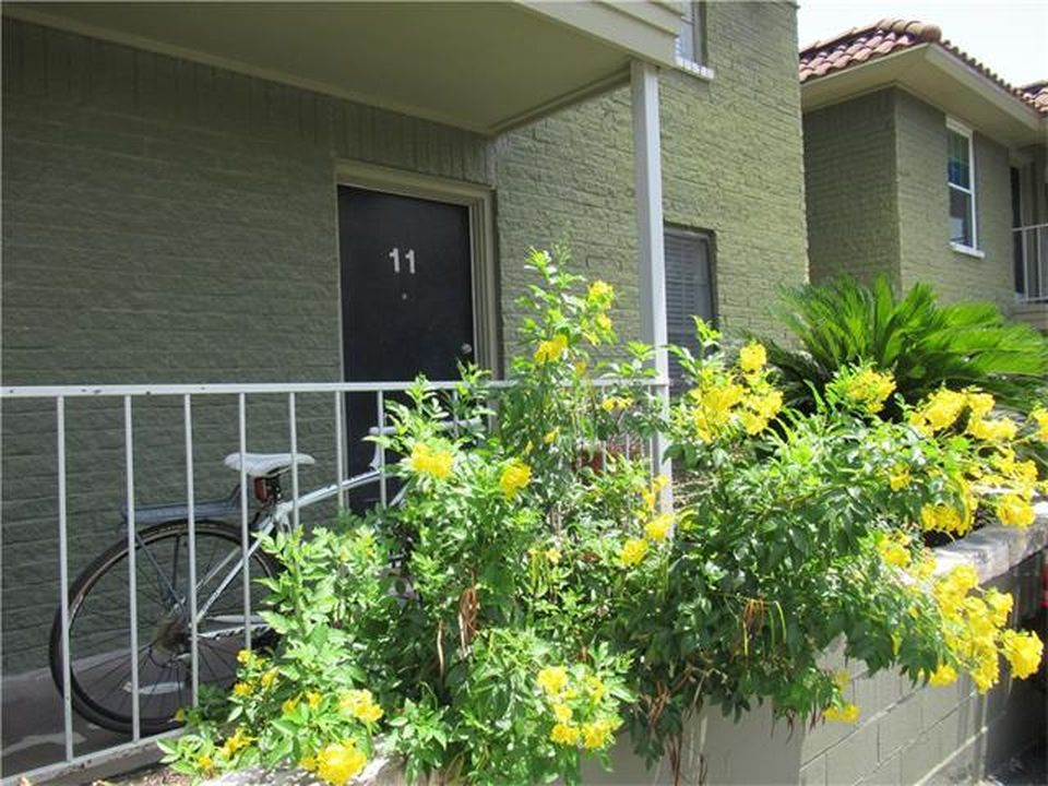 Dark green brick apartment building with yellow flowers in front