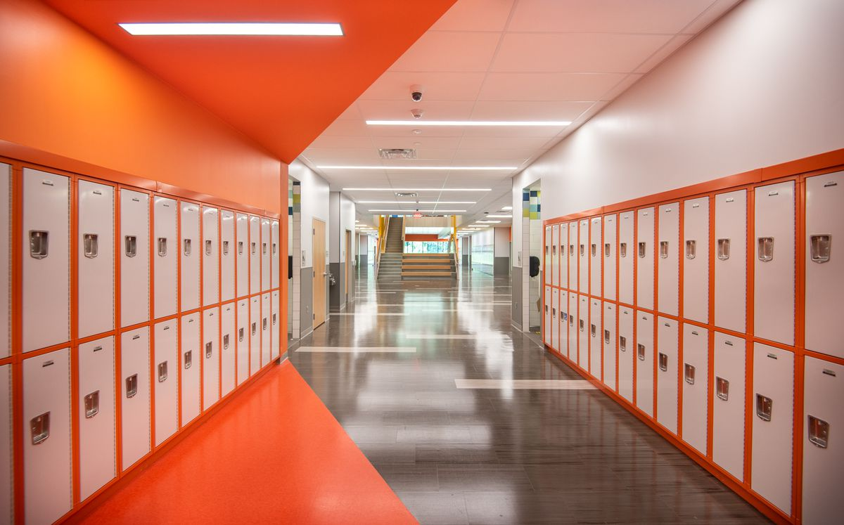 A hallway at the new Northeast Community Propel Academy, with white lockers lining the orange and white walls.