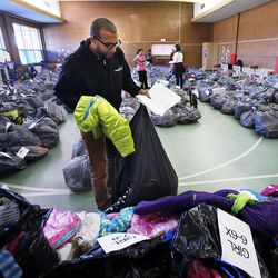 Shae Bourdeaux of Head Start fills bags during 2014 Operation Chimney Drop at Head Start in Salt Lake City, Monday, Dec. 15, 2014.