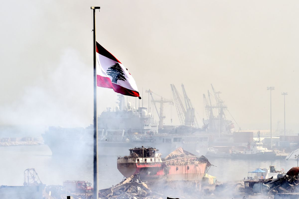 A flag flies over firefighters working at the scene of a warehouse fire at the Port of Beirut.