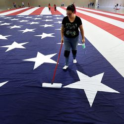 Rabecca Thomas cleans a giant American flag at the South Towne Expo Center in Sandy on Wednesday, May 31, 2017. The flag, which measures 78 feet by 125 feet, will fly between the two peaks at Grove Canyon in Pleasant Grove on the morning of July 4th. The organization Follow the Flag believes it will be the largest American flag ever flown.
