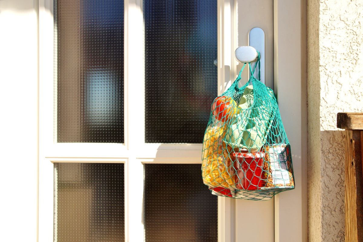A shopping bag with merchandise, goods and food is hanging on the knob of a front door.