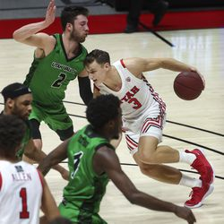 Utah Utes guard Pelle Larsson (3) drives on UVUWolverines forward Evan Cole (2) during game at the Huntsman Center in Salt Lake City on Tuesday, Dec. 15, 2020.